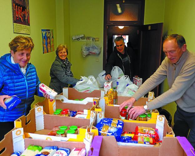 Los voluntarios de Cáritas del Juncal, ayer, ordenando los alimentos donados. /F. DE LA HERA