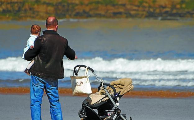 Un padre muestra el mar a su bebé en una playa. /