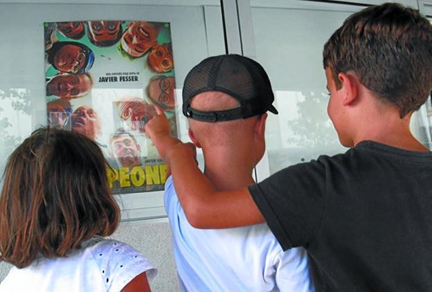Tres niños, uno de ellos con problemas de visión, observan el cartel