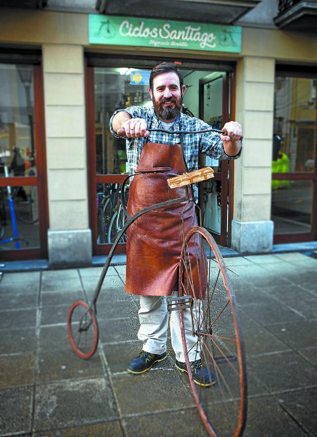 Iñaki Arana con el velocípedo que sirve de imagen y bienvenida en Ciclos Santiago./F. DE LA HERA