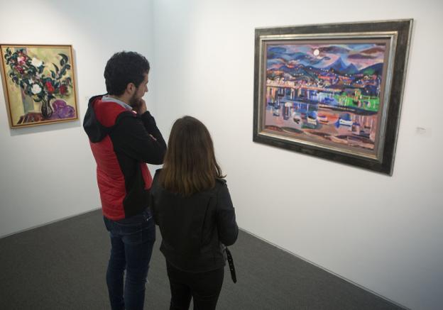 Dos visitantes observan 'Nocturno en el Bidasoa' en la muestra 'Vivir pintando, pintar viviendo'./F. DE LA HERA