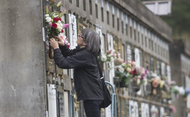 Una mujer coloca flores frescas, ayer en un nicho de Blaia. / F. DE LA HERA